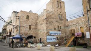 أشخاص يسيرون بالقرب من منازل تابعة ليهود في مدينة الخليل بالضفة الغربية، 12 نوفمبر، 2018. (Gershon Elinson/Flash90)