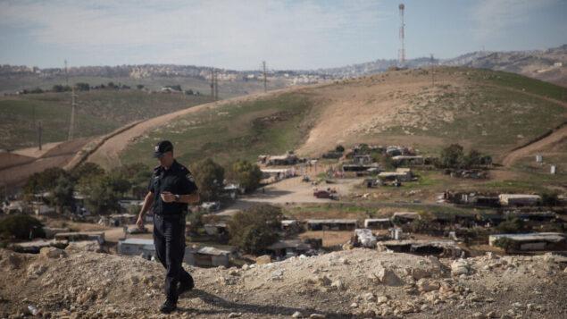 شرطي إسرائيلي على قمة تل يطل على قرية خان الأحمر البدوية في الضفة الغربية، 1 يناير 2019. (Hadas Parush/Flash90)