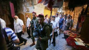 جنود إسرائيليون يوفرون الحراس لمستوطنين وزوار إسرائيليين خلال جولة في البلدة القديمة بمدينة الخليل، الضفة الغربية، 13 يوليو، 2019.  (Wisam Hashlamoun/Flash90)