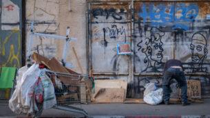 رجل يبحث في القمامة في حي فلورنتين في تل أبيب، 12 نوفمبر 2019 (Sara Klatt/FLASH90)