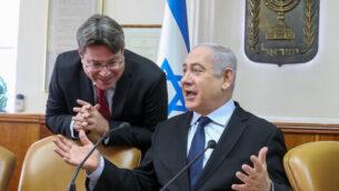 رئيس الوزراء بنيامين نتنياهو يتحدث مع وزير العلوم، أوفير أكونيس (يسار) في مستهل الجلسة الأسبوعية للحكومة في 22 ديسمبر، 2019 في مكتب رئيس الوزراء بالقدس. (Marc Israel Sellem/Pool/Flash90)