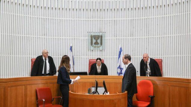 رئيسة المحكمة العليا إستر حايوت (وسط) تصل إلى جلسة استماع أولية للمحكمة العليا حول ما إذا كان يمكن تكليف مشرع يواجه لائحة اتهام جنائية بتشكيل ائتلاف، 31 ديسمبر 2019. (Yonatan Sindel / Flash90)