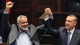 إسماعيل هنية، قائد حماس في قطاع غزة، يسار ، ورئيس الوزراء التركي رجب طيب أردوغان يحييان المشرعين والمؤيدين لحزب العدالة والتنمية الذي يقوده أردوغان في البرلمان في أنقرة، تركيا، 3 يناير 2012 (AP)