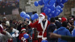 فلسطيني يرتدي زي بابا نويل يحمل بالونات في ساحة المهد، من أمام كنيسة المهد،  موقع ولادة يسوع المسيح بحسب المعتقدات المسيحية،. في مدينة بيت لحم بالضفة الغربية عشية عيد الميلاد، 24 ديسمبر، 2014.(AP Photo/Majdi Mohammed/File)