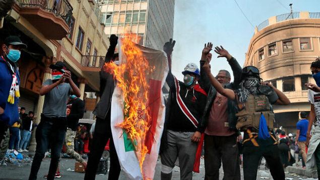 متظاهرون مناهضون للحكومة العراقية يحرقون علما إيرانيا خلال تظاهرات في بغداد، العراق، 29 نوفمبر، 2019. (AP Photo/Hadi Mizban)