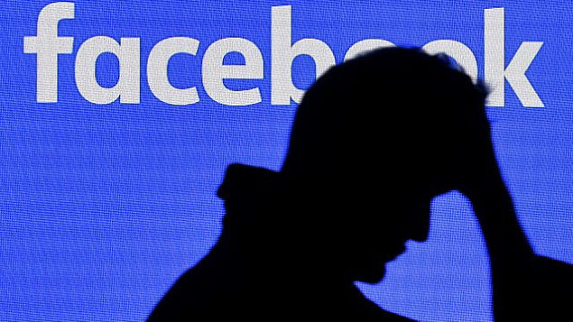 توضيحية: رجل يمر من أمام شاشة ل'فيسبوك' في معرض Gamescom في مدينة كولون الألمانية، 20 أغسطس، 2019.  (AP Photo/Martin Meissner)