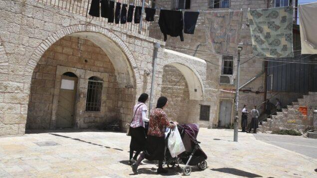 صورة توضيحية: نساء يهوديات متشددات يدفعن عربات أطفالهن أثناء السير في حي ميئا شعاريم اليهودي المتشدد في القدس، 4 يوليو 2013. (Nati Shohat / Flash90)