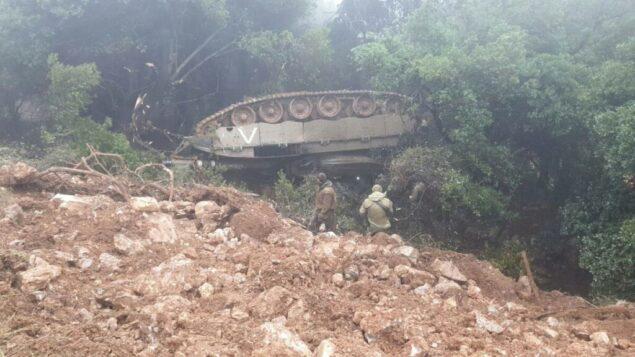 جنود يتفقدون دبابة تابعة للجيش الإسرائيلي انقلبت خلال تدريب في شمال إسرائيل، 9 ديسمبر 2019. (Courtesy)