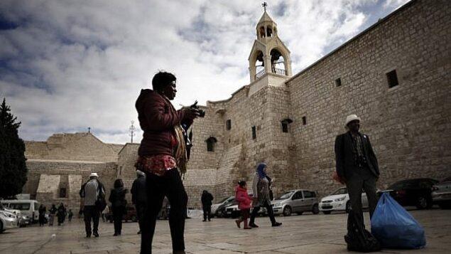 سياح وحجاج مسيحيون يتلقطون صورا من أمام كنيسة المهد في مدينة بيت لحم بالضفة الغربية، 12 ديسمبر، 2018.(Thomas Coex/AFP)
