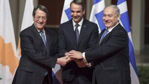 رئيس الوزراء بنيامين نتنياهو (يمين) ونظيره اليوناني كيرياكوس ميتسوتاكيس (وسط) والرئيس القبرصي نيكوس أناستاساديس يتصافحون في أثينا يوم 2 يناير 2020، قبل توقيع اتفاقية لمشروع خط أنابيب 'إيست ميد' لشحن الغاز من شرق البحر المتوسط إلى أوروبا. (Aris Messins/AFP)