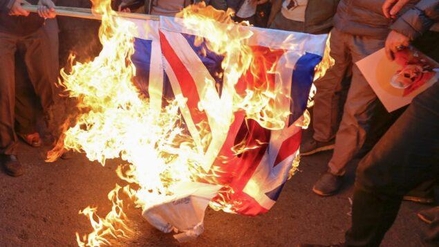 متظاهرون إيرانيون يقومون بإشعال النار في العلم البريطاني أمام السفارة البريطانية في العاصمة الإيرانية طهران، بعد اعتقال السفير البريطاني بزعم حضوره مظاهرة غير قانونية، 12 يناير 2020 (ATTA KENARE / AFP)
