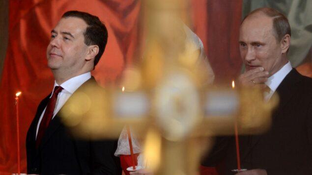 من الأرشيف: في هذه الصورة التي تم التقاطها في 5 مايو، 2013 يظهر الرئيس الروسي فلاديمير بوتين (يمين) ورئيس الوزراء ديمتري مدفيديف (يسار) يشاركان في احتفالات عيد الفصح الأرثوذكسي في كاتدرائية 'المسيح المخلص' بموسكو.  (Photo by Kirill KUDRYAVTSEV / AFP)