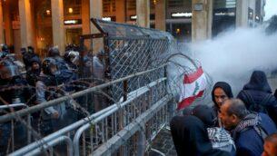 متظاهرون لبنانيون مناهضون للحكومة يتجمعون على الطريق المؤدي إلى البرلمان في وسط بيروت بينما يتصاعد الدخان من قنابل الغاز المسيل للدموع، 19 يناير 2020. (PATRICK BAZ/AFP)