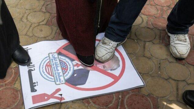 متظاهرون فلسطينيون يدوشون على صورة للرئيس الأمريكي دونالد ترامب خلال تظاهرة ضد إعلانه المتوقع عن خطته للسلام، في رفح بجنوب قطاع غزة، 28 يناير، 2020. (SAID KHATIB / AFP)
