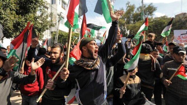 متظاهرون فلسطينيون يهتفون شعارات ويرفعون الأعلام الفلسطينية في تظاهرة ضد خطة السلام المتوقعة للرئيس الأمريكي دونالد ترامب في مدينة غزة في 28 يناير، 2020.   (MAHMUD HAMS / AFP)