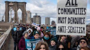 اشخاص يشاركون في مسيرة تضامن مع اليهود في جسر بروكلين، 5 يناير 2020 في مدينة نيويورك. (Jeenah Moon/Getty Images/AFP)