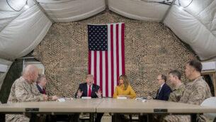 الرئيس الأمريكي دونالد ترامب، يرافقه مستشار الأمن القومي جون بولتون، الثالث من اليسار، السيدة الأولى ميلانيا ترامب، الرابعة من اليمين، السفير الأمريكي في العراق دوغ سيليمان، الثالث من اليمين، والقيادة العسكرية العليا، يتحدث إلى صحفيين في قاعدة الأسد الجوية في العراق، 26 ديسمبر 2018. (AP Photo / Andrew Harnik)