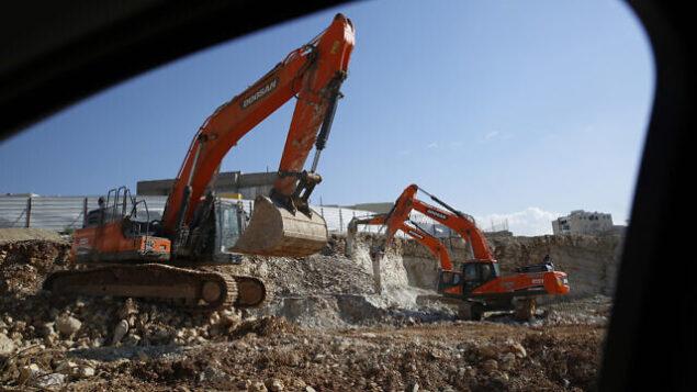 في هذه الصورة التي تم التقاطها في الاول من يناير، 2019، يظهر رجال وهم يعملون في مشروع سكني جديد في مستوطنة موديعين عيليت بالضفة الغربية. (AP Photo/Ariel Schalit)