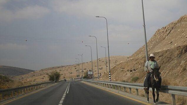 رجل فلسطيني يمتطي حمارا على طريق رئيسي في غور الأردن، بالقرب من بلدة طابوس بالضفة الغربية، 11  سبتمبر، 2019.  (Ariel Schalit/AP)