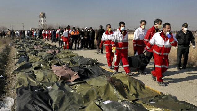 عمال الإنقاذ يحملون جثة أحد ضحايا تحطم الطائرة الأوكرانية في شاهد شهر، جنوب غرب العاصمة الإيرانية طهران في 8 يناير، 2020.  (AP Photo/Ebrahim Noroozi)