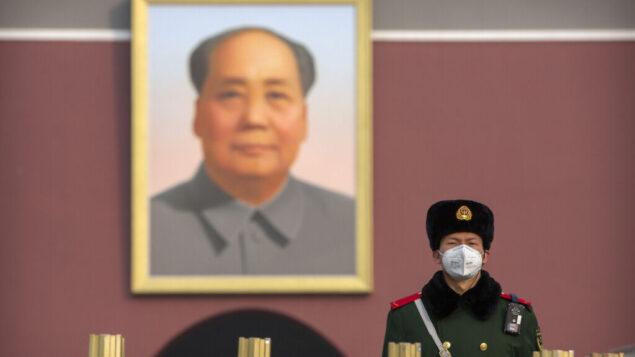 رجل شرطة شبه عسكري يرتدي قناعًا للوجه بالقرب من الصورة الكبيرة للزعيم الصيني ماو تسي تونغ عند بوابة تيانانمن المتاخمة لساحة تيانانمين في بكين، 27 يناير 2020. (AP Photo / Mark Schiefelbein)