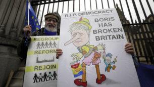 مناهضون لخروج بريطانيا من الاتحاد الأوروبي يحملون لافتات خارج البرلمان في لندن، 30 يناير 2020. (AP Photo / Kirsty Wigglesworth)