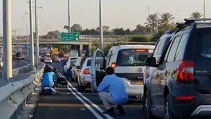 لقطة شاشة من مقطع فيديو يظهر فيه سائقون إسرائيليون وهو يجلسون بجانب مركباتهم على طريق سريع بعد انطلاق صفارات الإنذار محذرة من إطلاق صواريخ من قطاع غزة، 12 نوفمبر، 2019.  (Twitter)