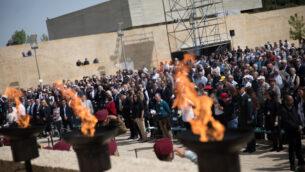 الجمهور يقف للنشيد الوطني الإسرائيلي في نهاية حدث تذكاري في متحف ياد فاشيم للهولوكوست بينما تحيي إسرائيل يوم ذكرى الهولوكوست السنوي في البلاد، 12 أبريل 2018. (Hadas Parush / Flash90)