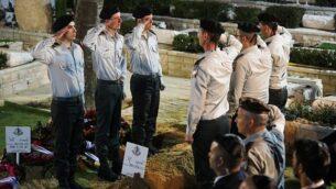 جنود إسرائيليون يلقون التحية العسكرية أمام قبر الجندي زخاريا باومل، الذي فُقدت آثاره خلال معركة 'سلطان يعقوب' في عام  1982، خلال جنازته في المقبرة العسكرية 'جبل هرتسل' بالقدس، 4 أبريل، 2019.  (Hadas Parush/Flash90)