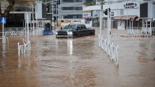 سيارة تسير على طريق غمرته المياه في مدينة نهاريا الشمالية، 8 يناير 2020. (Meir Vaknin / Flash90)