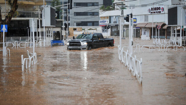 مركبة تسير في طريق غمرته المياه في مدينة نهاريا شمال البلاد، 8 يناير، 2020.  (Meir Vaknin/Flash90)
