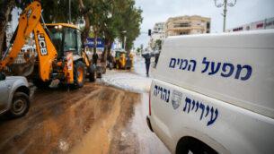 عمال بلدية نهاريا يعملون في شوارع المدينة الواقعة في شمال البلاد والتي عانت من فيضانات قوية بسبب سقوط أمطار غزيرة، 9 يناير، 2020. (David Cohen/Flash90)