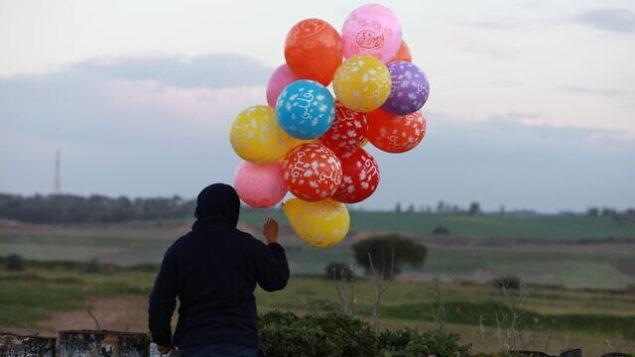 صورة توضيحية: مجموعة من البالونات الحارقة تجهز قبل اطلاقها نحو إسرائيل، بالقرب من الحدود بين إسرائيل وغزة، شرقي مخيم البريج للاجئين في وسط قطاع غزة، 22 يناير 2020. (Ail Ahmed / Flash90)