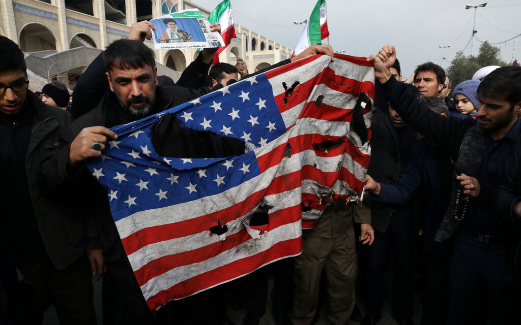 متظاهرون يحرقون العلم الأمريكي خلال مظاهرة ضد قتل الجنرال الإيراني قاسم سليماني في طهران، 3 يناير 2020. (AP Photo / Vahid Salemi)