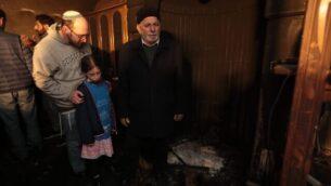 (من اليسار) أب وابنته يقفان إلى جانب المختار إسماعيل عواد خلال زيارة تضامنية إلى مسجد في شعفاط تم إحراقه في جيمة كراهية مفترضة، 25 يناير، 2020.  (Tag Meir)