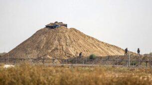 صورة توضيحية: صورة التقطت من خان يونس في جنوب قطاع غزة تظهر جنود إسرائيليين يتفقدون المنطقة المحيطة بموقع مراقبة بجوار السياج الحدودي مع القطاع الساحلي في 1 أغسطس 2019، بعد تبادل نيران مع مسلح فلسطيني (Said Khatib/AFP)