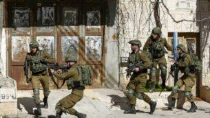 جنود إسرائيليون يوجهون بنادقهم خلال اشتباكات مع فلسطينيين بعد مداهمة في منطقة بيت لحم هذا الصباح بحثًا عن مشتبه به مطلوب في هجوم دهس في القدس في وقت سابق، أسفر عن إصابة 12 جنديًا، أحدهم بجروح خطيرة، 6 فبراير 2020 (Musa Al SHAER / AFP)