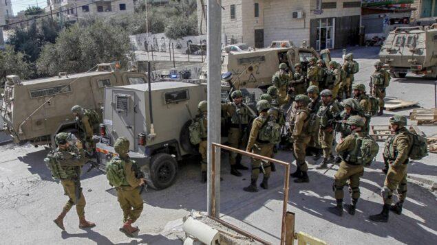 جنود إسرائيليون خلال مداهمة في منطقة بيت لحم بحثًا عن مشتبه به مطلوب في هجوم دهس في القدس في وقت سابق، أسفر عن إصابة 12 جنديًا، أحدهم بجروح خطيرة، 6 فبراير 2020 (Musa Al SHAER / AFP)