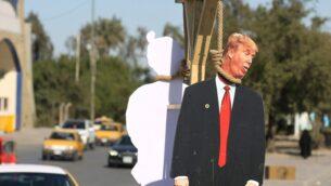 مجسّم كرتوني للرئيس الأميركي دونالد ترامب وجنديًا من الجيش الأمريكي (من الخلف) معلقين من مشنقة رمزية على طول شارع في ضاحية مدينة الصدر بشرق بغداد، 10 فبراير 2020 (AHMAD AL-RUBAYE / AFP)