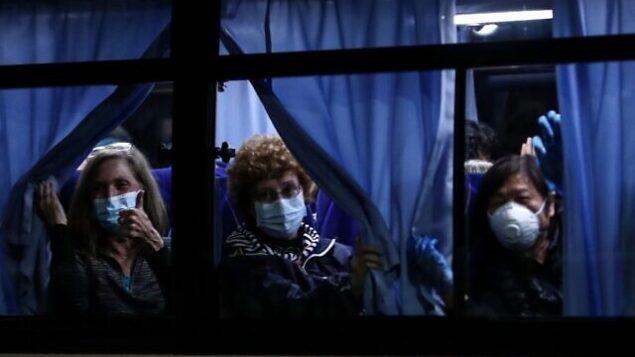 مسافرون أمريكيون يغادرون رصيف 'دايكاكو بير كروز' في ميناء يوكوهوما، بالقرب من سفينة 'دايموند برينسس' السياحية الخاضعة لحجر صحي بسبب مخاوف من انتشار فيروس كورونا COVID-19،  في 17 فبراير، 2020. (Behrouz MEHRI / AFP)