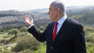رئيس الوزراء بنيامين نتنياهو يقف في موقع يطل على حي هار حوما بالقدس الشرقية، 20 فبراير 2020. (Debbie Hill/Pool/AFP)