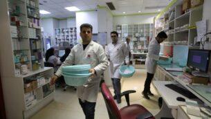 """الطاقم الطبي الإيراني يعمل في صيدلية """"13 آبان"""" الحكومية في طهران، 19 فبراير 2020 (ATTA KENARE / AFP)"""