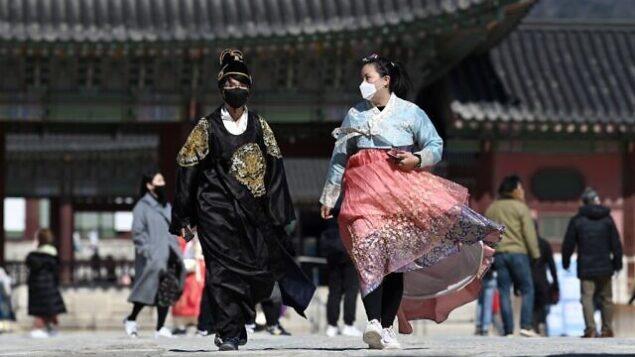 امرأتان ترتديان الزي التقليدي الكوري وتضعان قناعي وجه خلال زيارة إلى قصر  غيونغبوك في سول، 23 فبراير، 2020.  (Jung Yeon-je / AFP)