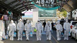 عمال سوق يرتدون الملابس الواقية ويرشون المطهر في سوق في مدينة دايغو، بكوريا الجنوبية، 23 فبراير،.  2020 كإجراء وقائي بعد تفشي فيروس كورونا. (YONHAP / AFP)