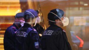 شرطيون يضعون أقنعة واقية خلال إغلاقهم لفندق بالقرب من مدينة إنسبروك النمساوية، في 25 فبراير، 2020 بعد أن تم تأكيد إصابة امرأة عملت هناك بفيروس كورونا.  ( Johann GRODER / APA / AFP)