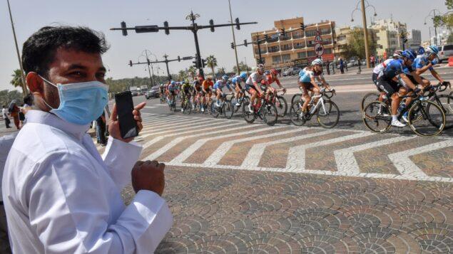 رجل يرتدي قناع جراحي ينظر بينما تنطلق المجموعة خلال المرحلة الخامسة من جولة الإمارات للدراجات من المروم إلى جبل حفيت، في دبي، 27 فبراير 2020. (Giuseppe CACACE / AFP)