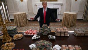 الرئيس الأمريكي دونالد ترامب يتحدث إلى وسائل الإعلام حول طاولة مليئة بالوجبات السريعة في غرفة الطعام بالبيت الأبيض في واشنطن، 14 يناير 2019، لحضور حفل استقبال لفريق كليمسون تايغرز. (AP Photo/Susan Walsh)