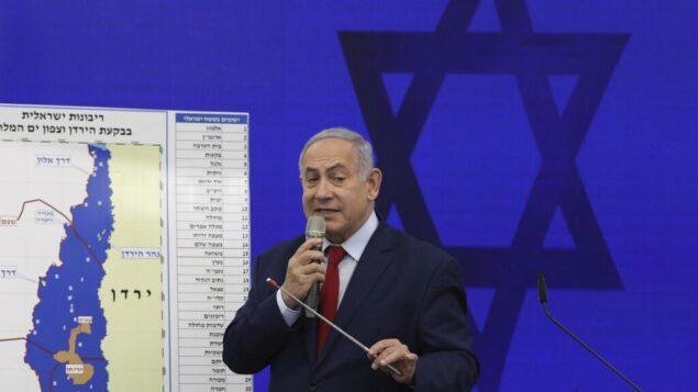 رئيس الوزراء بنيامين نتنياهو يدلي ببيان وهو يقف أمام خريطة لغور الأردن، ويتعهد بفرض السيادة الإسرائيلية على غور الأردن ومنطقة شمال البحر الميت، في رمات غان، 10 سبتمبر، 2019. (AP Photo/Oded Balilty)