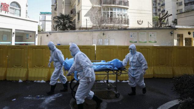 عاملون في المجال الطبي ينقلون شخصًا توفي بسبب COVID-19 في مستشفى في ووهان بمقاطعة هوبى بوسط الصين، 16 فبراير 2020  (Chinatopix via AP)
