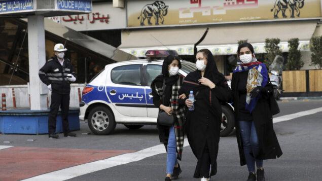 صورة توضيحية: أحد رجال الشرطة والمشاة يرتدون أقنعة للحماية من فيروس كورونا، في وسط طهران، إيران، 23 فبراير 2020. (Ebrahim Noroozi / AP)
